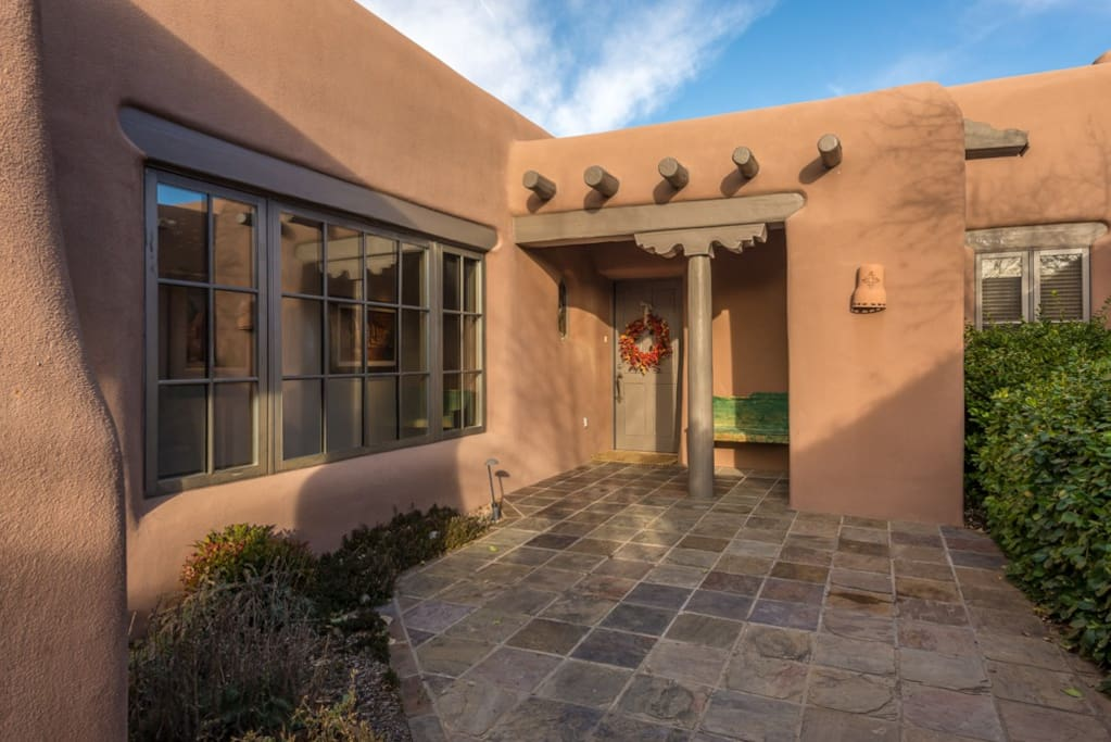 Enclosed patio with authentic vigas and adobe architecture.