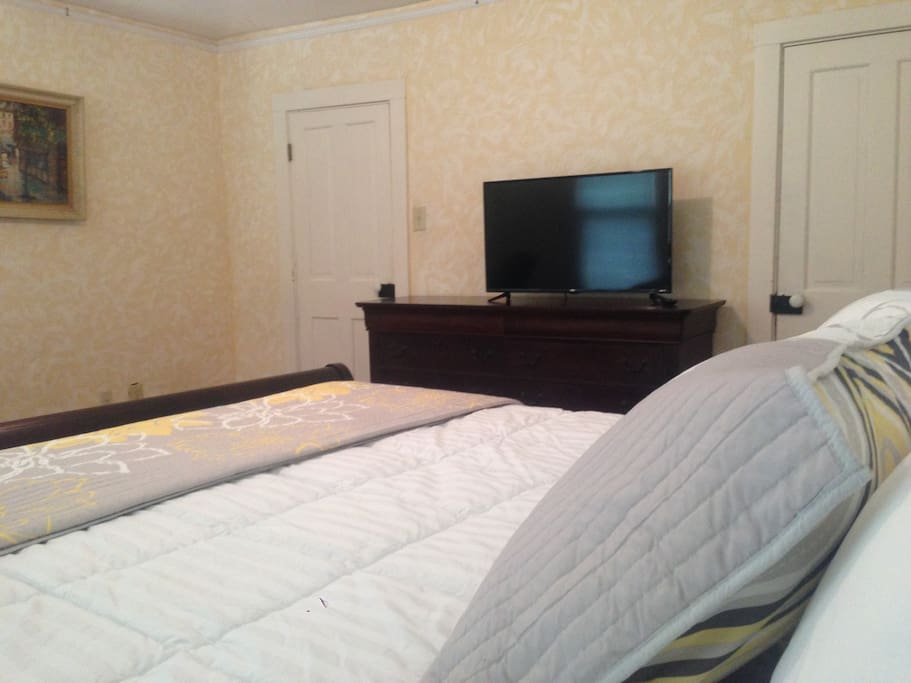 """New 40"""" TV with built-in Roku and solid wood vanity in king bedroom"""