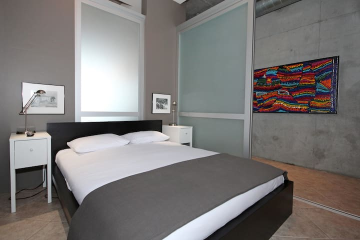 Second bedroom; queen bed, wall-mounted TV and state-of-the-art sliding door system