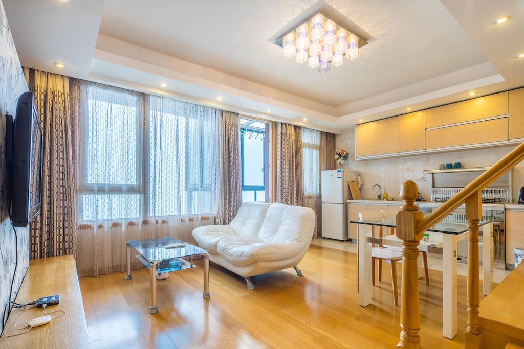 客厅,拉上里层窗帘的样子,非常温馨,可以在此闲适地看电视。边上是小厨房和餐桌
