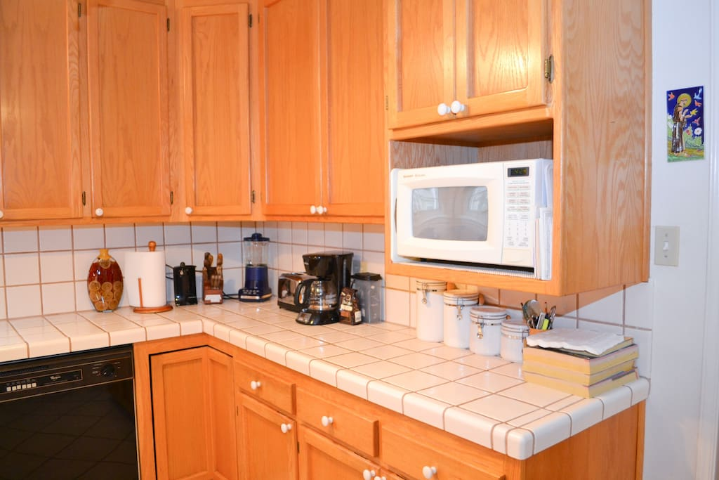 Partial view of kitchen with tile counter tops and all the necessary cooking amenities.