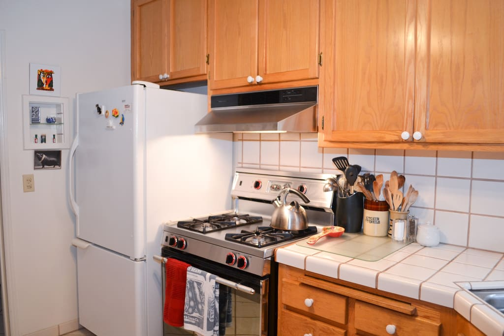 Gas range and oven, refrigerator & freezer combo. Tile counter tops and oak cabinets.