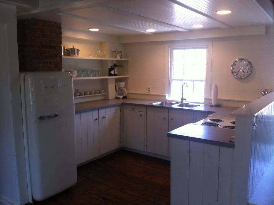 Another view of your full kitchen with modern amenities, new appliances (SMEG refrigerator, stove/oven, microwave, toaster oven and coffee maker), including original cabinets, windows and wide-plank hardwood floors.