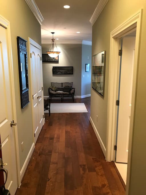 This is the entrance from the hallway to the condo. Left door is the laundry room and right door is the guest full bathroom. Ahead is a sitting area.