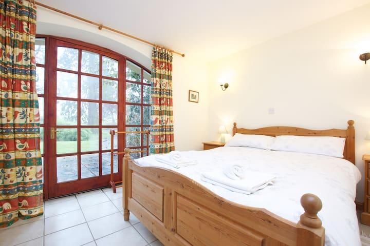 Kingsize bedroom with patio doors opening onto private garden