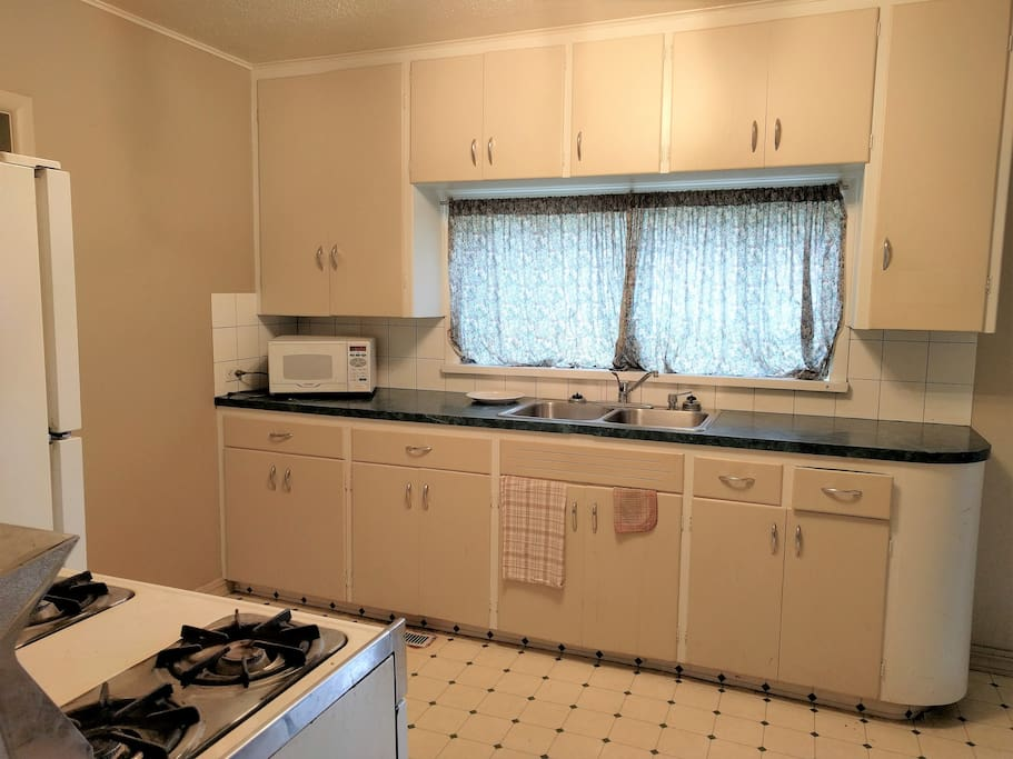 Kitchen with microwave, range, and full-sized fridge