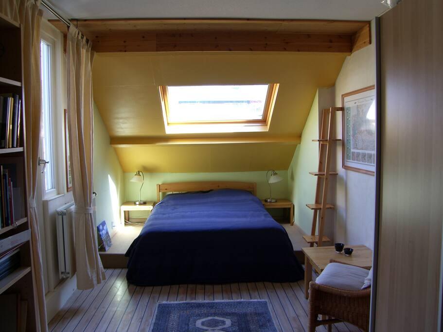 De ruime kamer met het 2persoonsbed. Links is een deur met een groot hor.