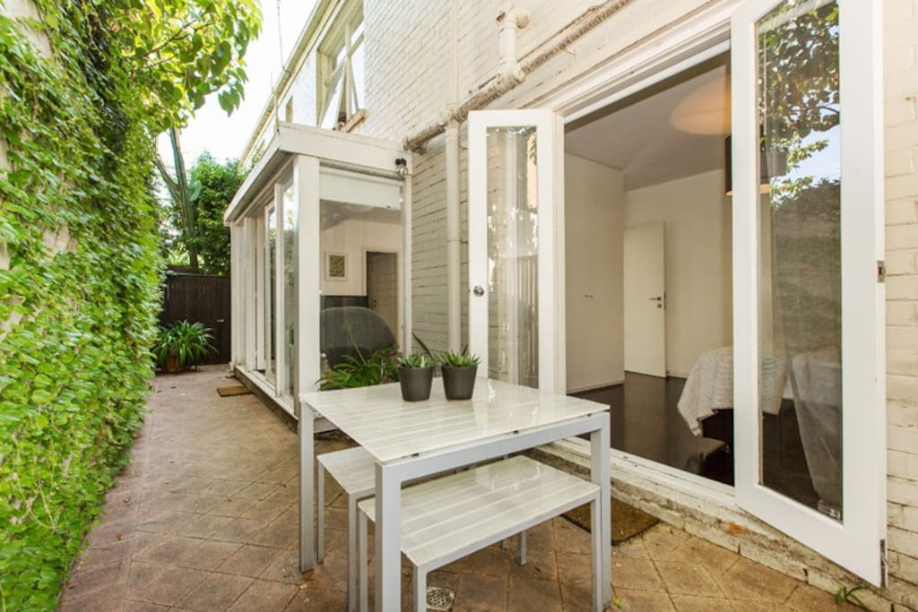 Private leafy rear courtyard with outdoor dining.