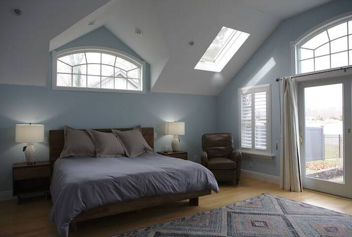 Master bed with king-sized bed, en-suite, walk-in closet, waterfront view and sliding glass doors to garden (with tomatoes, peppers, herbs and more)!