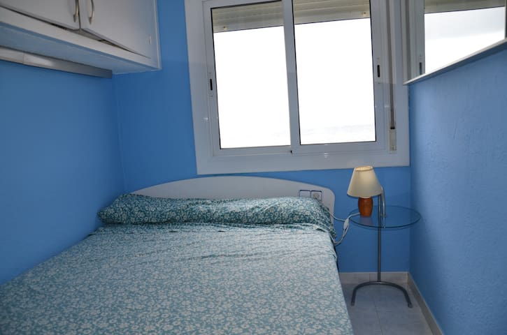 cama doble con ventana sobre el mar