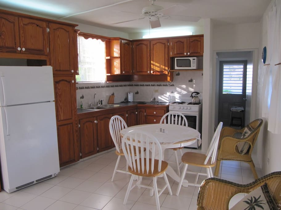Open kitchen and sitting area, with full sized gas stove, fridge and microwave...