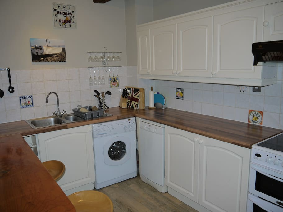 Attractive pine units, with fridge freezer, electric cooker, microwave, washer/drier & dishwasher. Toaster, coffee maker, iron, electric kettle are all included.