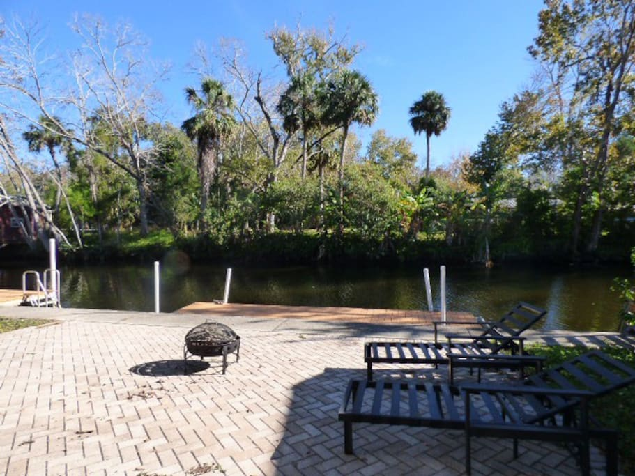 Private backyard with fire pit, floating dock for easy launching on the included kayaks, paddleboard and canoe.