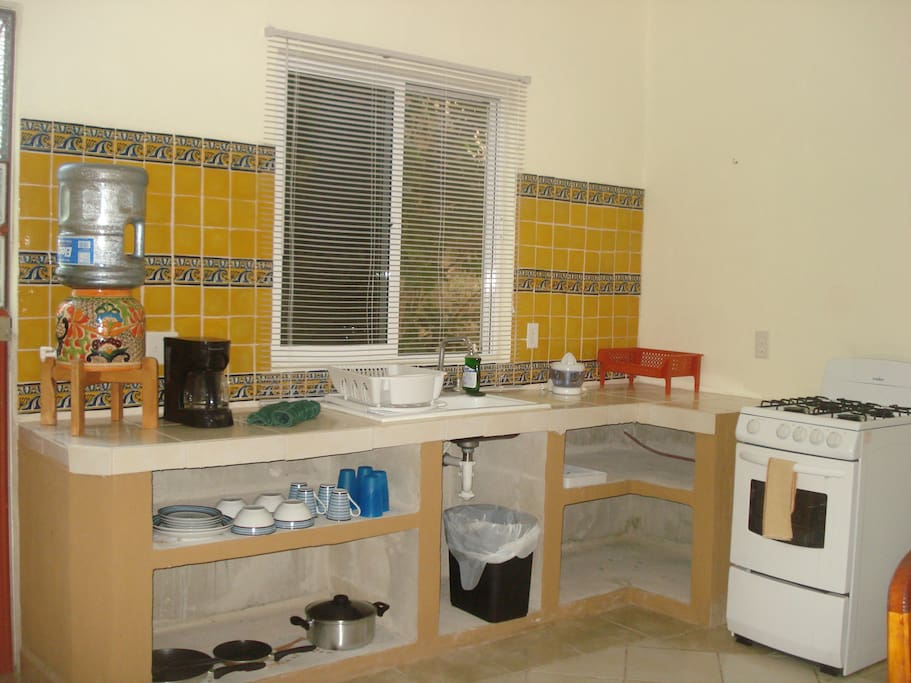 Kitchen in unit number 4, complete with stove, oven, microwave, coffe maker and refrigerator.
