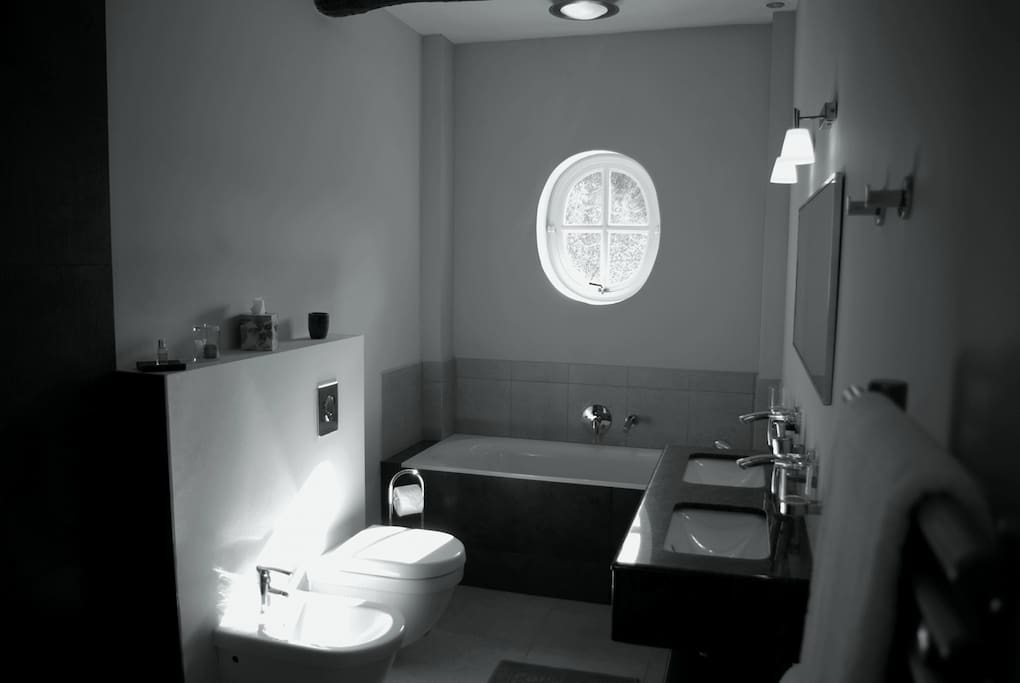 The Autan wetroom bathroom with bidet, toilet, bath, double sink and waterfall shower.