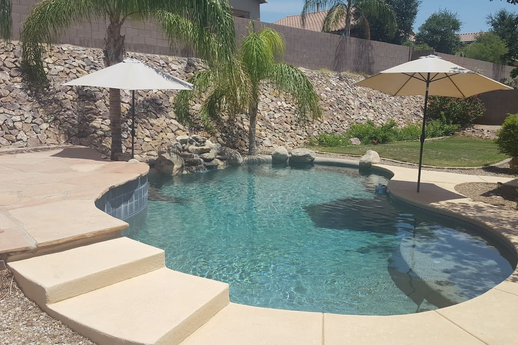 Peaceful and private pool with waterfalls, sundeck, umbrellas, and palm trees