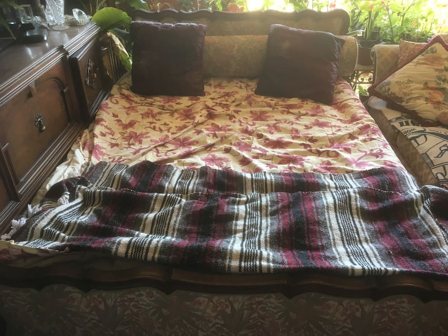 queen size bed from 1940s with tall air mattress next to sofa in same retro style with 52 inch flat panel Tv above wood cabinets