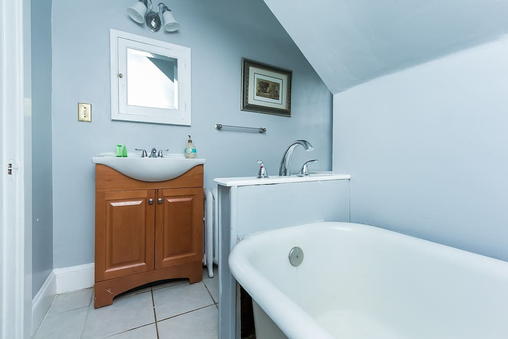 Bright bathroom with just tub no shower