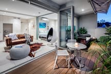 Chic open plan studio (with sliding glass wall for optional private bedroom space) flowing out to huge deck with daybed and powered sun awning.