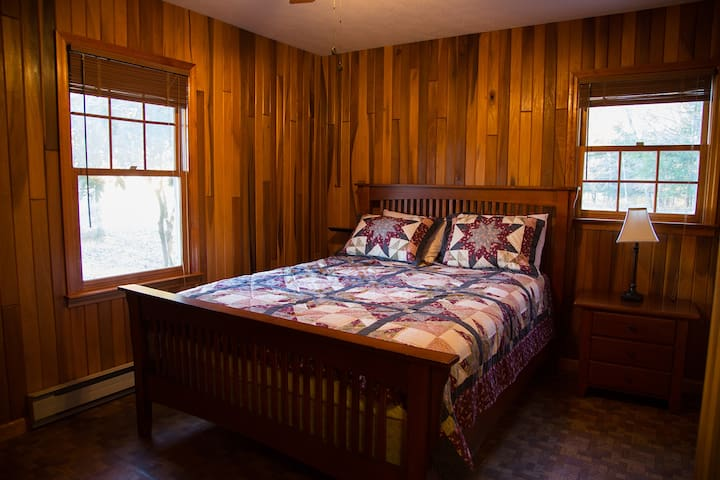 2nd bedroom w/ queen bed and fine wood furnishings and paneling