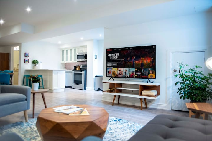 Bright and spacious living room with television, couches, and chair for entertaining and relaxing