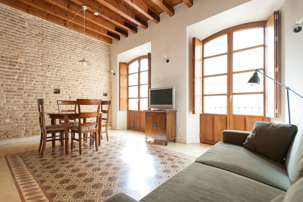 Bright living room featuring exposed brick walls, beams and original floor tiles.