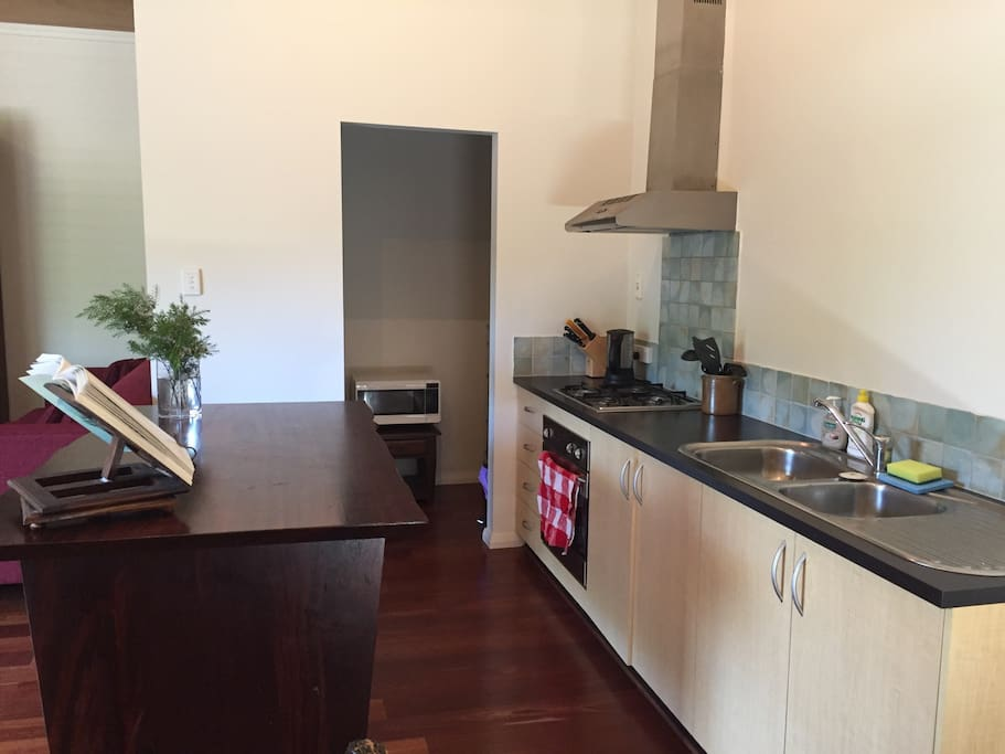 Spacious kitchen with kettle, toaster, microwave, fridge, stove, eating utensils and more