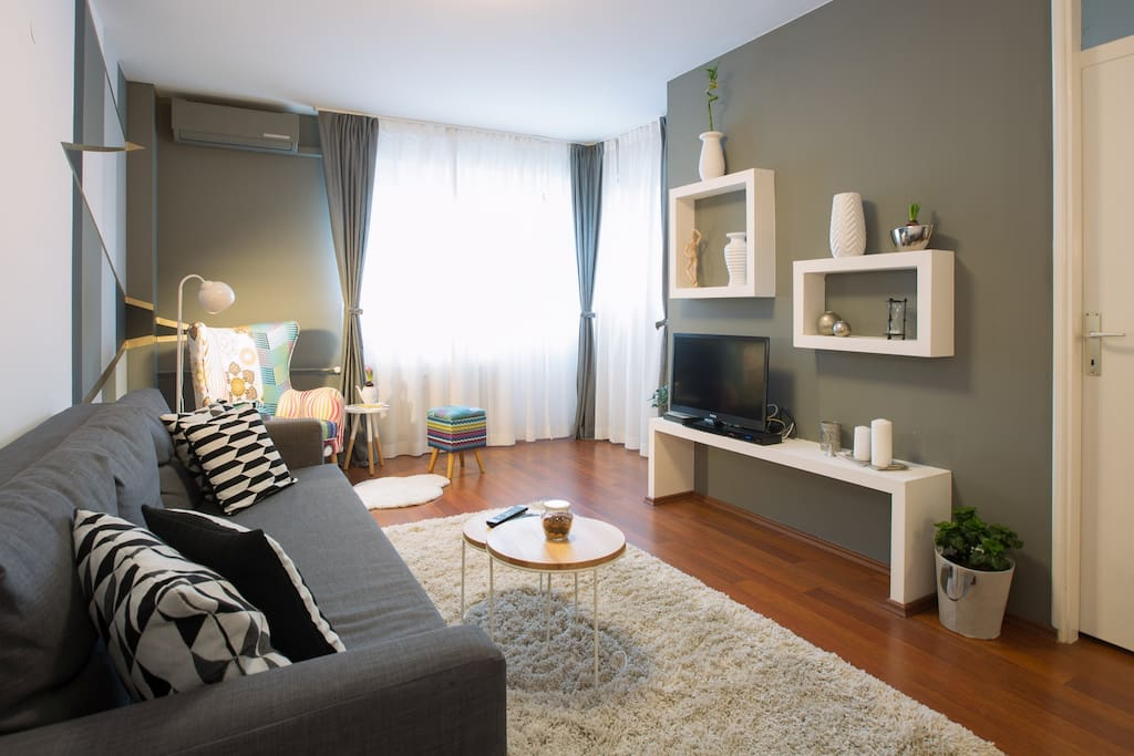 living room with double sofa bed, tv, armchair end exit to the terrace.
