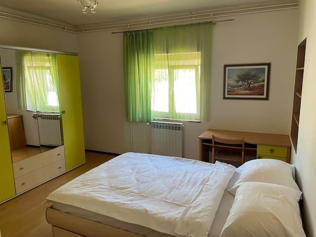 Pogled u ogledalo iz kreveta. U ormarima dodatna posteljina. Radni stol.