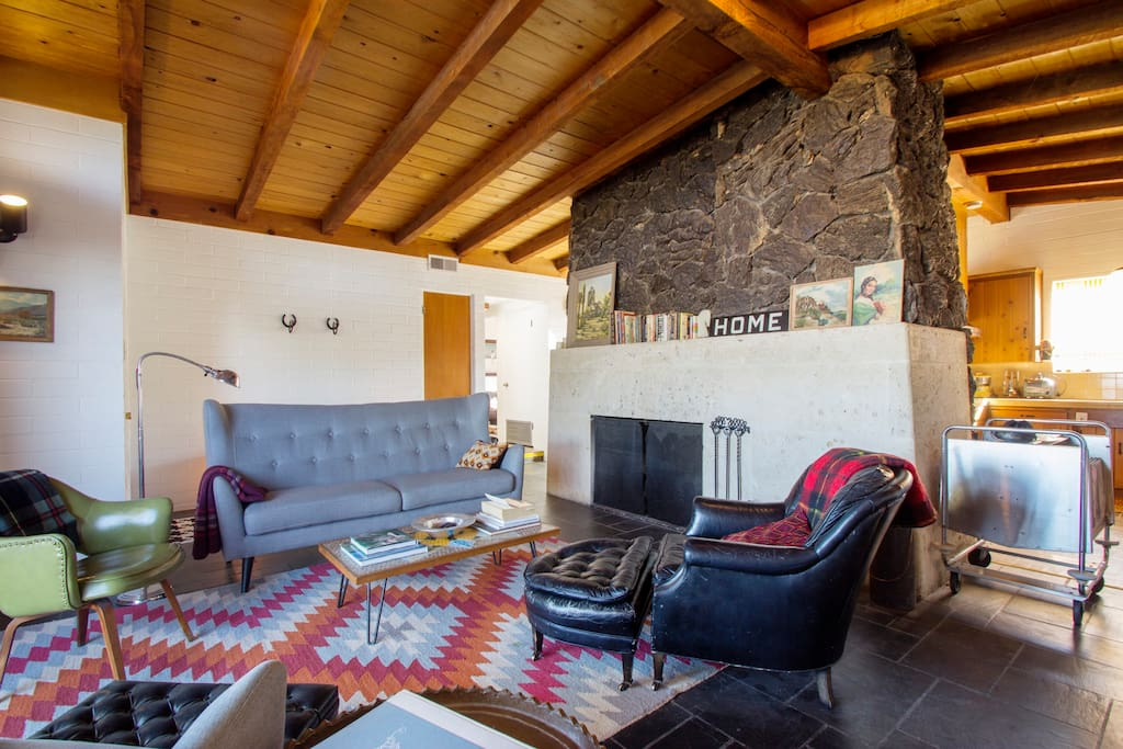 Exposed beams and massive lava rock and Texas limestone fireplace in the living room.