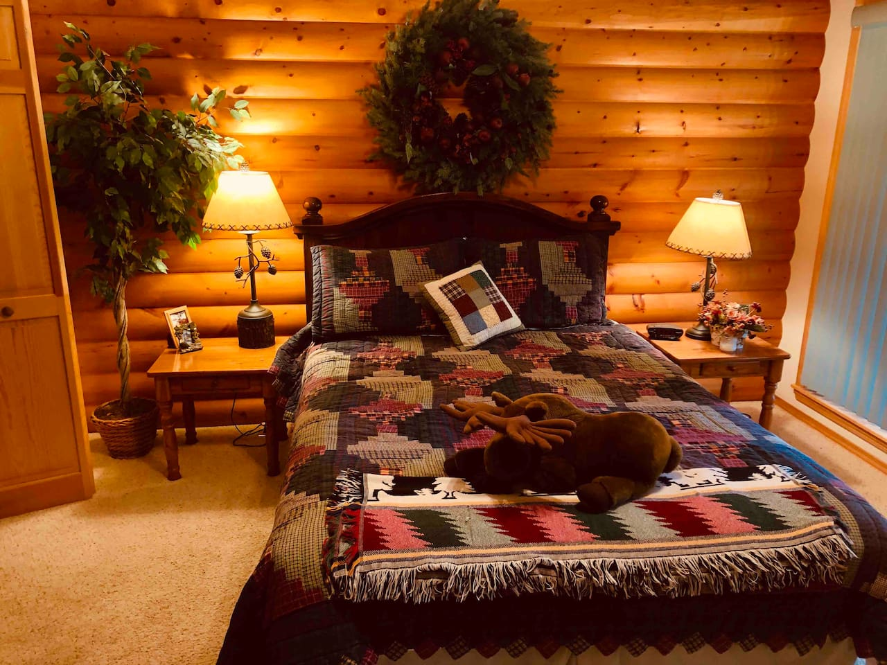 Master bedroom queen bed with log-siding and knotty pine