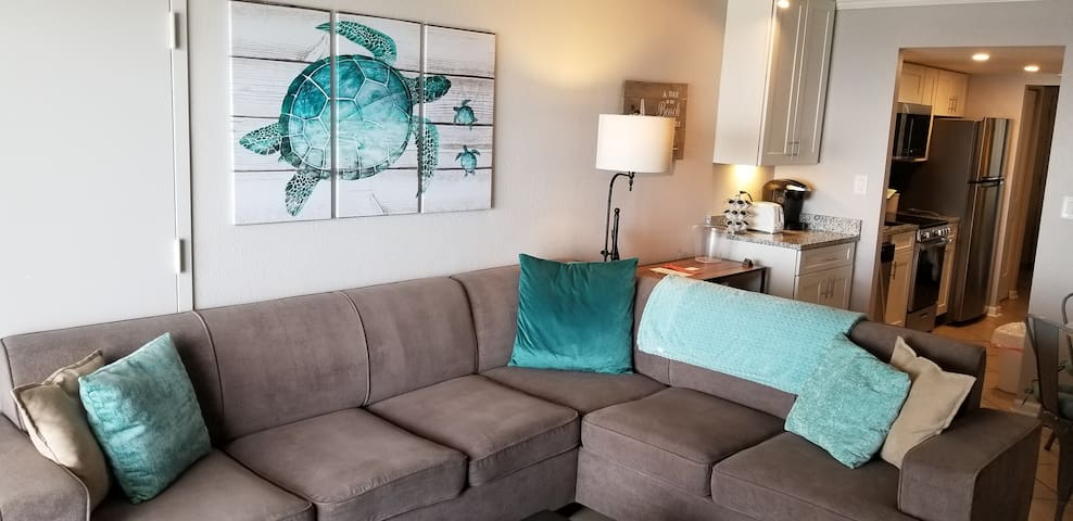 """Living room with queen sleeper sectional, 50"""" UHD smart tv, breakfast bar with Keurig plus table & chairs for 4."""