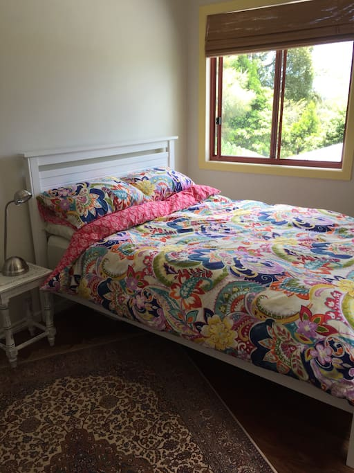 Bright and colourful bedroom with Very comfortable double bed. Wake up listening to birds and looking out at trees and hills