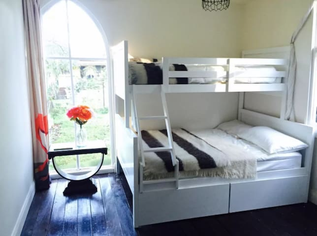 Downstairs bedroom: double bunkbed plus single bed at the top and a toddler bed or cot set up and wardrobe