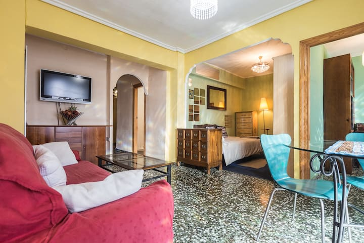 Sala de estar con balcón, televisión y cama extra / Living room