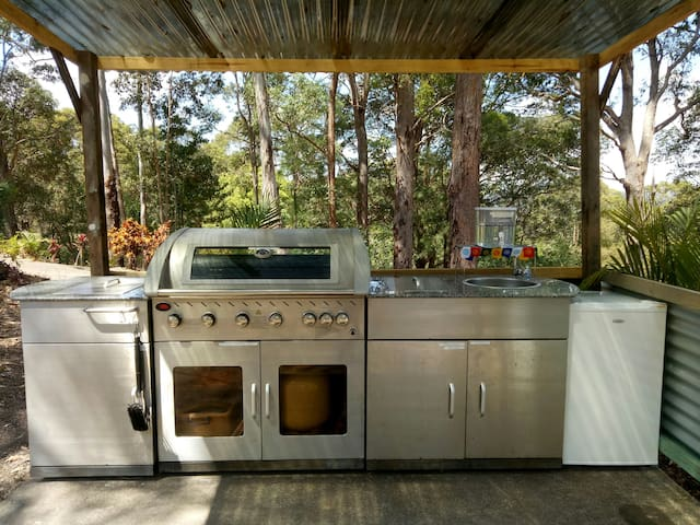 Camp kitchen with bbq, fridge, freezer, cook top, cooking utensils and serving plates, cups, etc