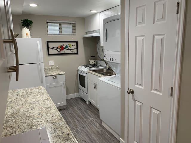 Kitchen includes microwave, stove, oven, toaster, coffee machine, blender, pots, pans, utensils for cooking and eating, dishes, and stocked with essential spices, condiments, snacks and beverages