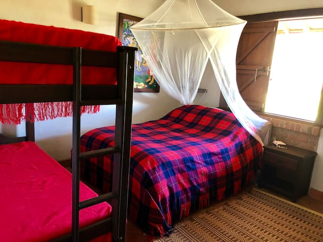 Bedroom with double bed and bunkbed, with a shared bath