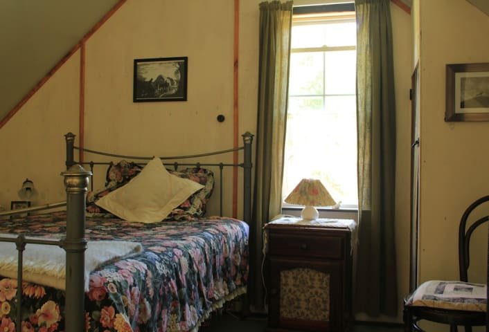 The upstairs bedroom overlooks the garden, orchard and forests.