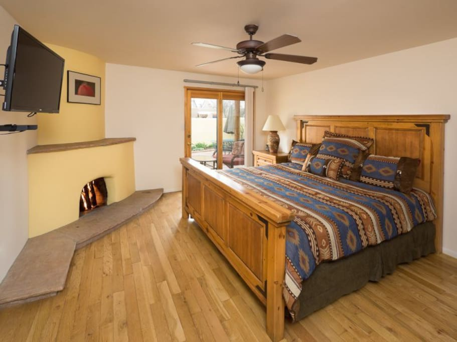 Master bedroom with queen bed, flat-screen tv, and exit to back patio