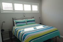Spacious sunny bedroom, with queen bed and side tables.  Also mirrored built in wardrobes with extra linen and ironing  board.