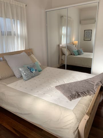 Spacious second bedroom with queen bed, air-conditioning and large built-in wardrobes.