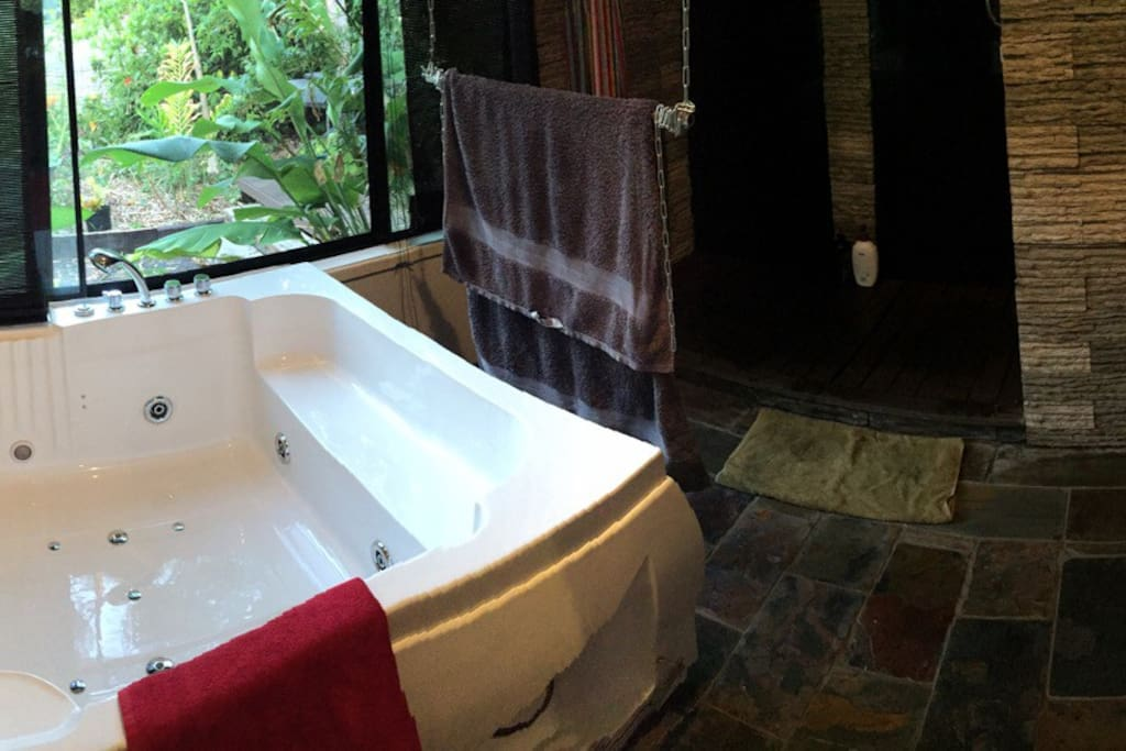 Bathroom with twin spa, twin shower and twin basins. Views of the tropical garden