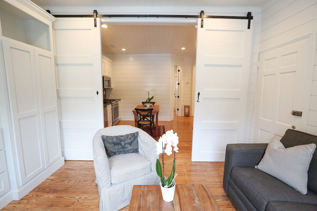 Extra-tall vintage barn doors slide all the way open to create a large open-concept living area flowing into the kitchen and foyer.