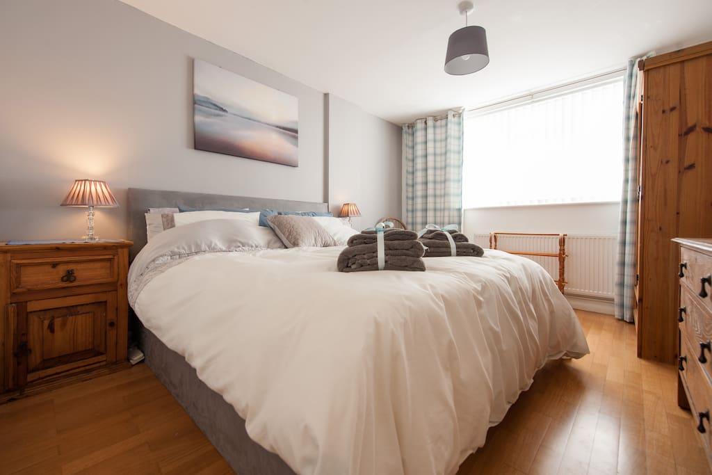 Double bedroom with Super-king size bed, Oak dressing table, Bedside tables with charger points and Wardobe with wooden hangers.