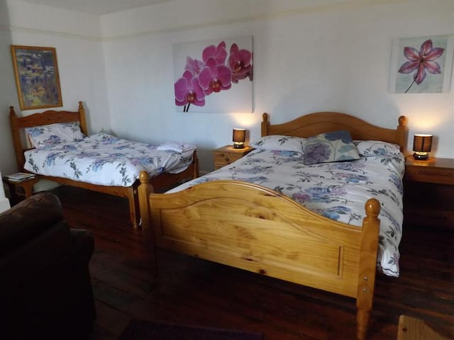 A spacious room with one double and one single bed