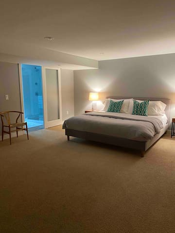 The lower-level bedroom suite features a king-sized Sleep Number bed with an attached bathroom with  double shower and heated floors. This room is quiet and cool - perfect for sleeping!