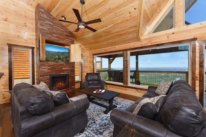 """Living room with 55"""" TV, fireplace and panoramic views."""