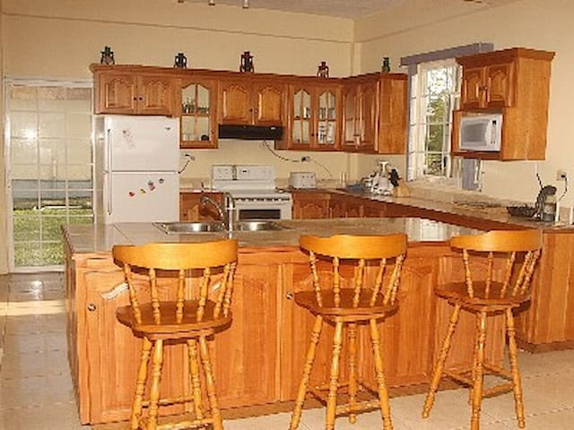 View of the Kitchen with island and stools.