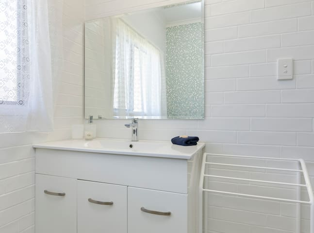 Our bathroom has a vanity and a walk-in shower with a separate toilet.   We provide toilet paper, hand soap and shampoo and conditioner.   There are bath towels, hand towels and bath mats.